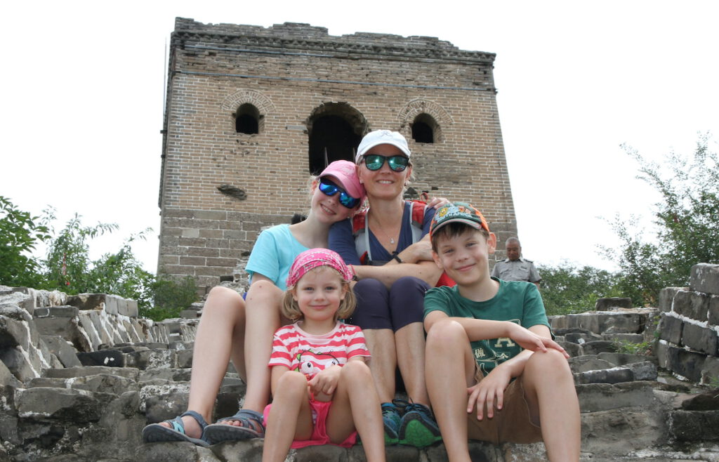 mom and three kids sitting at the Great Wall of China