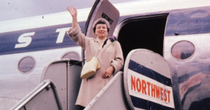 photo around 1965 of woman in hat waving as she boards a Northwest airlines flight
