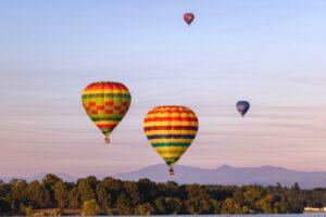 hot air ballons over hills